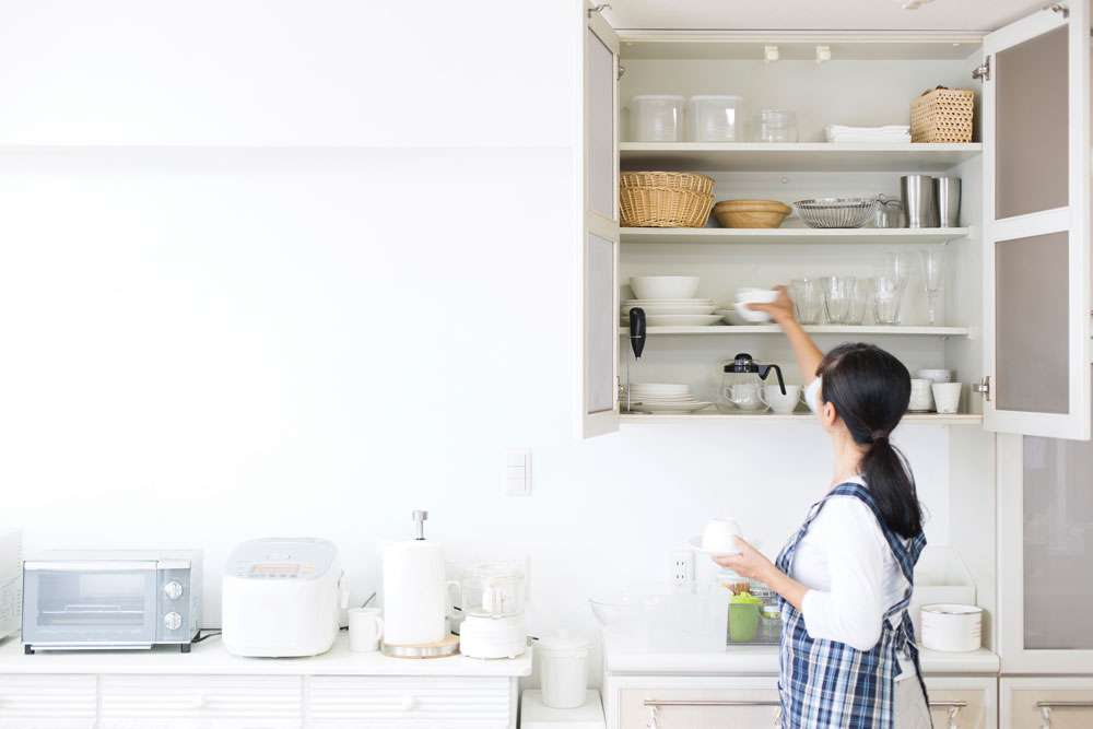 A woman placing bowls in her kitchen cabinet.