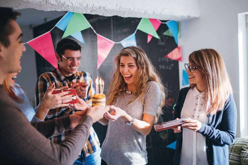 A group of friends celebrates a birthday with a small cake and candles.